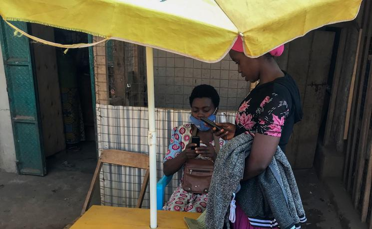 Vestina attending to a customer at her mobile money business in Kyangwali refugee settlement. Photo: LWF Uganda