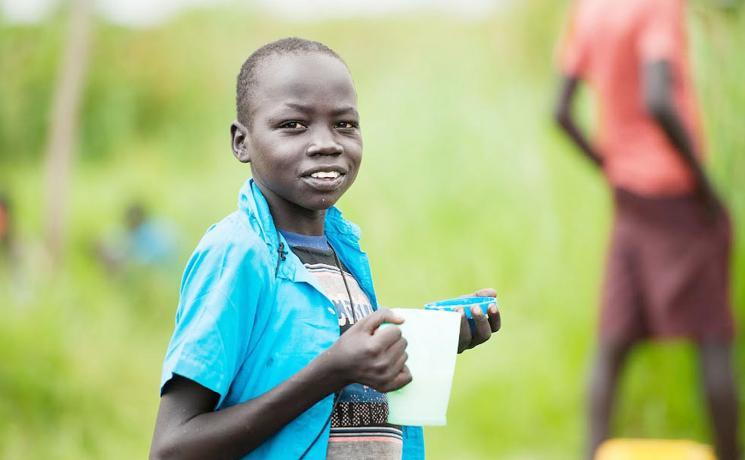 A young South Sudanese refugee eats porridge in Northern Uganda. Photos:LWF/Uganda
