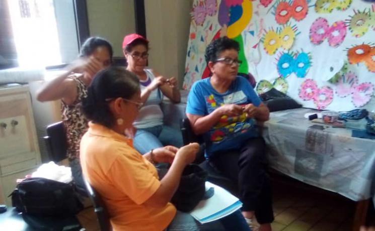 """Participants in a sewing workshop for mothers and other community members at the IELV-run """"House of Friendship."""" Everything here is made by hand, and the facilitator gives instructions the same way, as a sewing machine is unaffordable. All photos: IELV/Judith Bracho Villegas"""