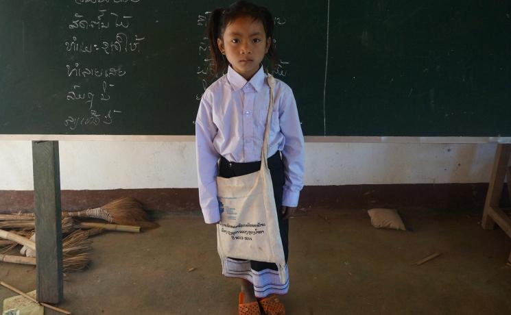 Chanset, an ethnic Khmu girl in northern Laos, with school uniform, books and other items provided by LWF as part of a program to provide access to quality education for girls. Photo: LWF/P. Simayvanh