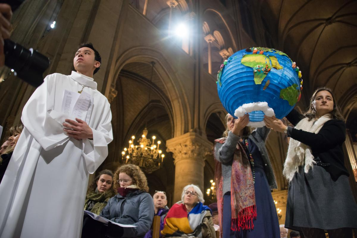 Youth hold symbols of creation during an ecumenical celebration at the Cathredral of Notre Dame de Paris during the COP 21 climate talks taking place in nearby Le Bourget, 3 December 2015 Photo: LWF/Ryan Rodrick Beiler