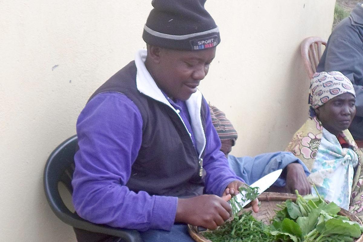 Sergio Banze prepares green vegetables for conservation in Tingonhamene village, Chokwe district, southern Mozambique. Photo: LWF Mozambique/Gilberto Banze
