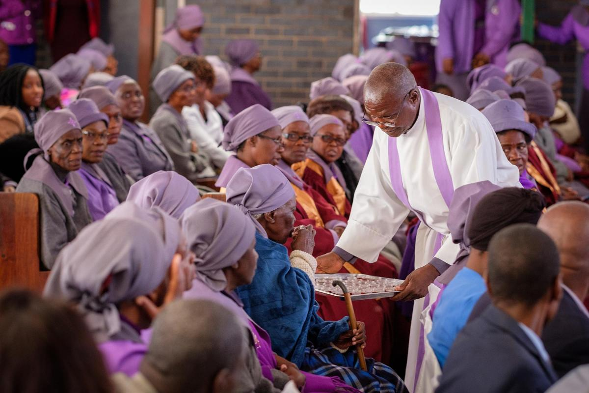 Before theCOVID-19 pandemic, the LWF General Secretary paid a solidarity visit to Zimbabwe.In this photo, a pastor distributesHoly Communion during worship at theNjubeCenterparish of the Evangelical Lutheran Church in Zimbabwe.Photo: LWF/A. Danielsson