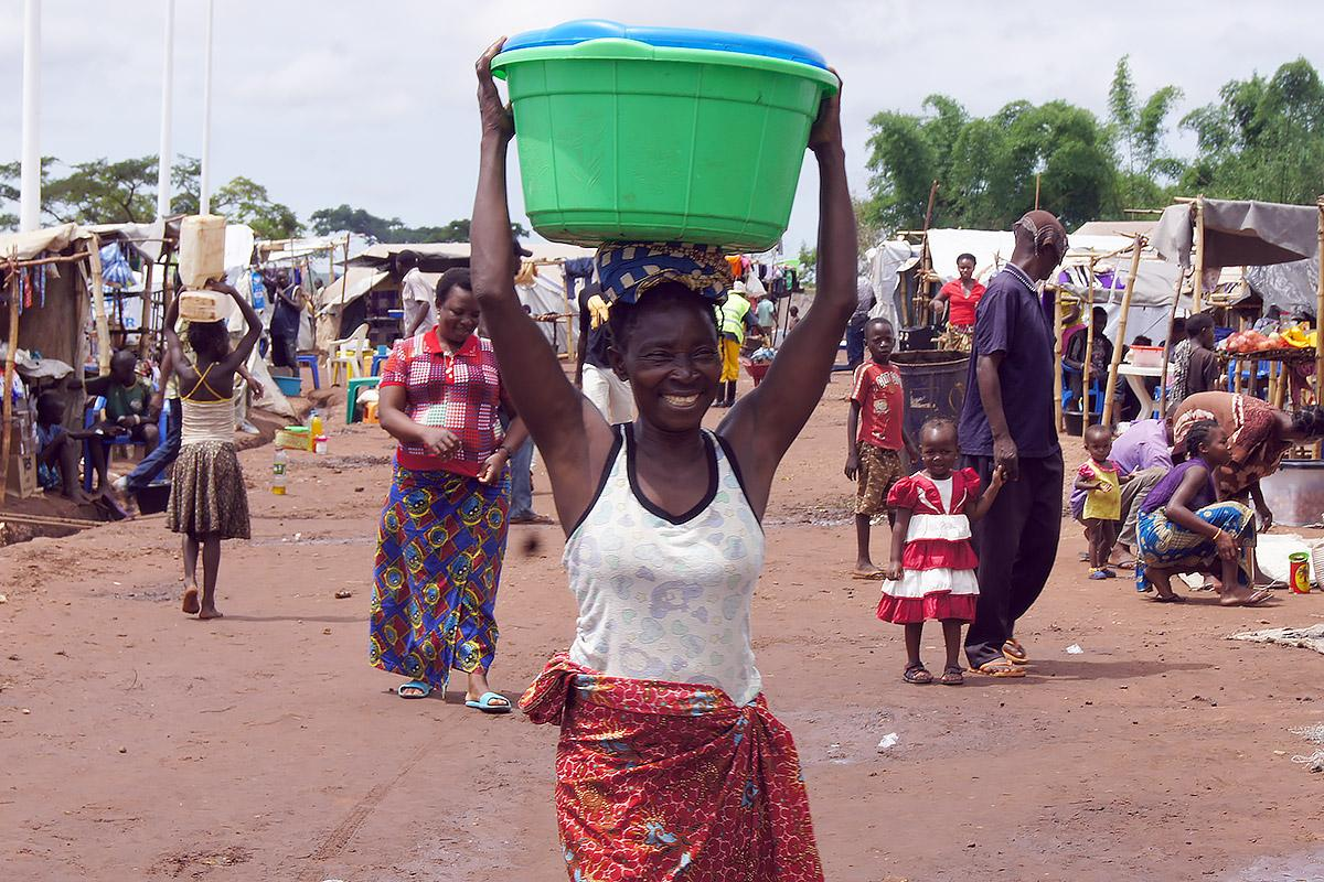 A woman carries water from a barehole installed by the LWF in Cacanda reception center, Northern Angola. Photo: LWF / C. Kästner