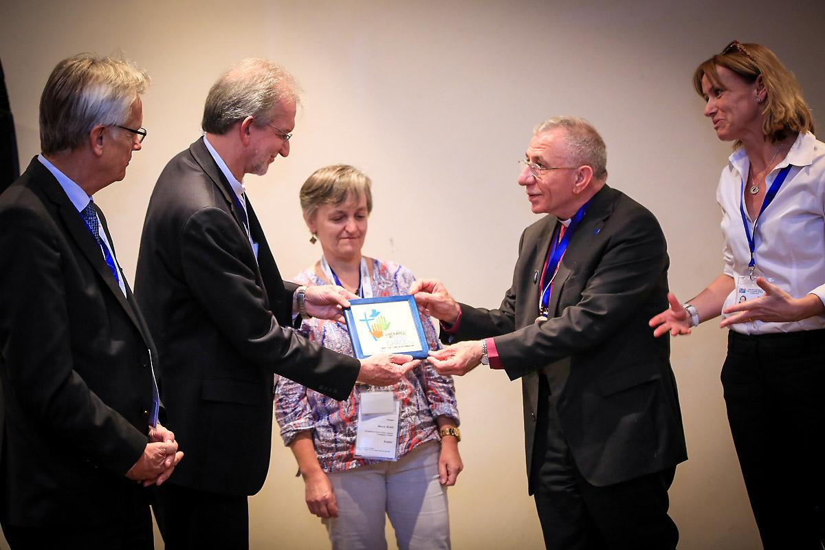 Marcia Blasi, Evangelical Church of the Lutheran Confession in Brazil, LWF General Secretary Martin Junge and Regional Program Coordinator Anne Caroline Tevoy look on as Bishop Munib Younan presents a decorative tile of the LWF Assembly logo to the Rev. Dr. Nestor Paulo Friedrich, Evangelical Church of the Lutheran Confession in Brazil. The Brazilian church made a gift to the AVH Hospital and the tile is a token of thanks. Photo: LWF/Johanan Celine Valeriano