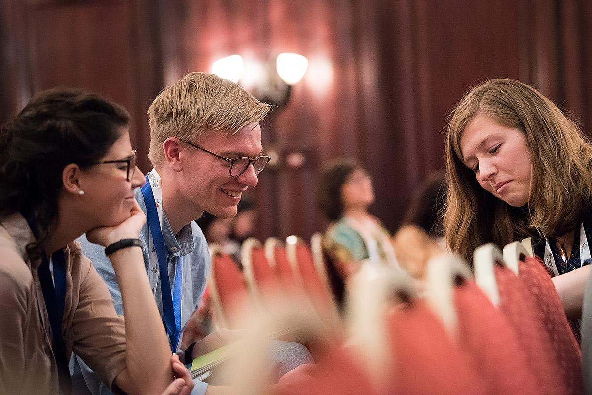 Paula Göhre (left) and Tim Sonnemeyer of the Evangelical Lutheran Church in Bavaria welcome their synod's decision to strengthen youth participation. Here they meet with Rebecca Lühmann of the Evangelical Lutheran Church of Hanover at the LWF Twelfth Assembly. Photo: LWF/Albin Hillert