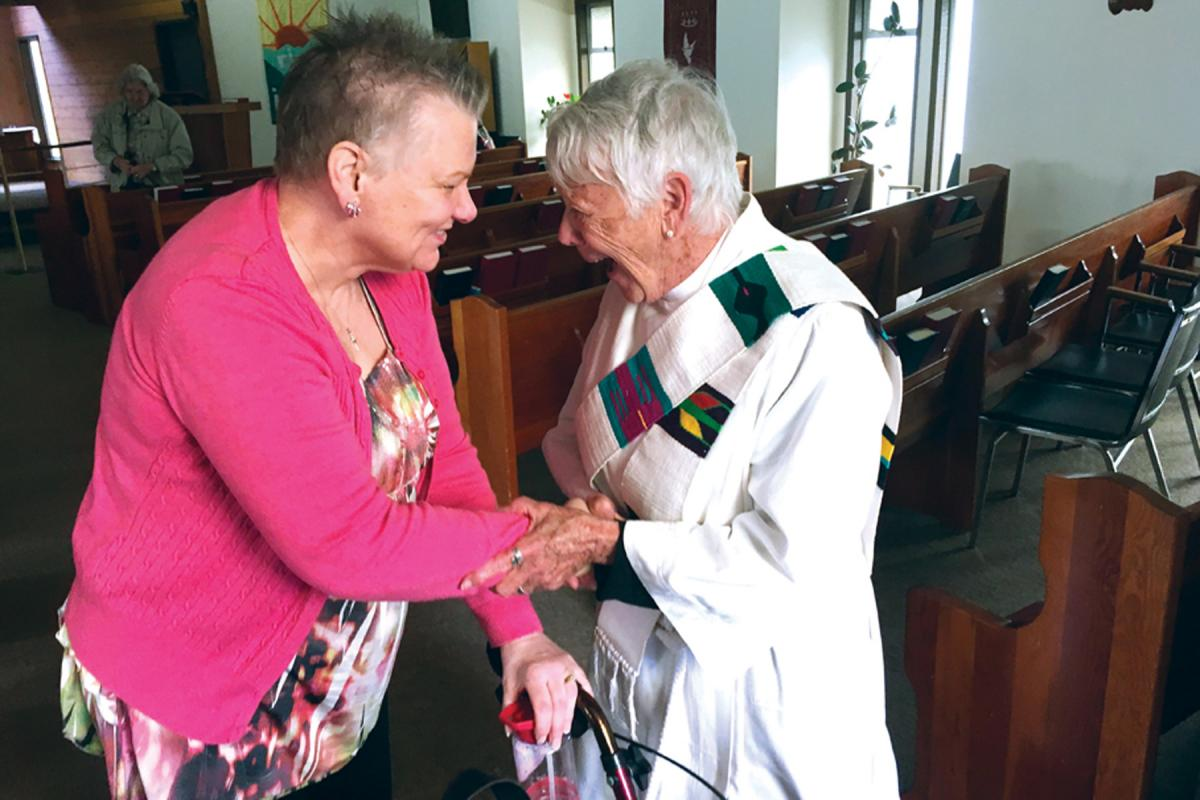 A minister greets a parishioner at the church at Faith, Province of British Columbia. Photo: Canada Lutheran