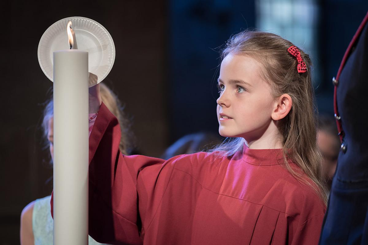 A girl lights a candle at Lund Cathedral, signifying one of the five ecumenical imperatives. Photo: LWF/Albin Hillert