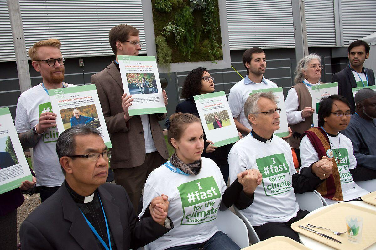 An interfaith group of religious leaders sits in front of empty trays during a public action at COP21 in Paris in 2015. Photo: LWF/Ryan Rodrick Beiler