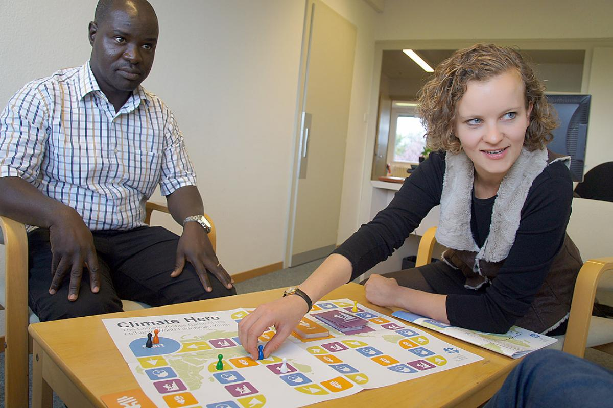 LWF program officer Lokiru Matendo Yohana (left) and youth secretary Caroline Richter come up with creative ideas for ending climate change as they play the LWF board game, Climate Hero. Photo: LWF/S. Cox
