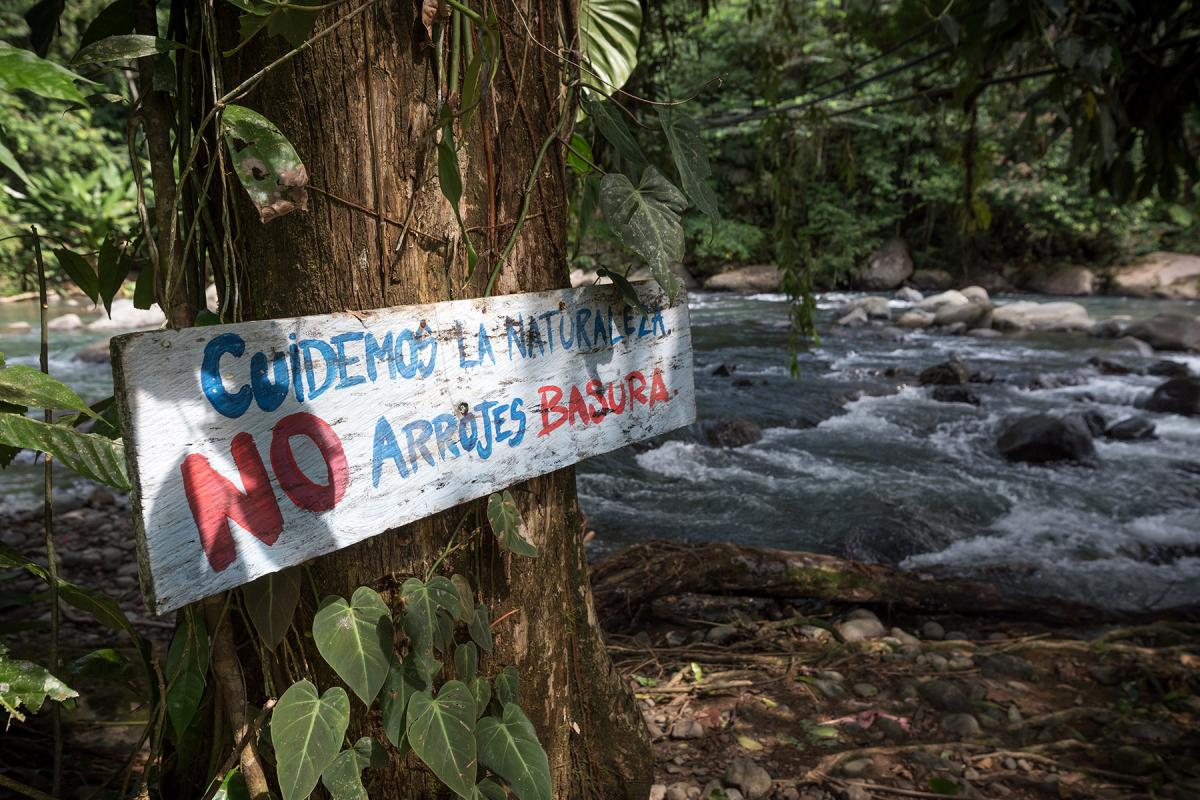 """'Take care of nature, do not litter,"""" reads a sign by the River Fortuna in San José de León, in northwest Colombia. The sign has been placed there by the local community, as a way of taking care of the life-giving asset of clean drinking water. While access to the river is key to the community, concerns abound that they will not be able to protect themselves against businesses looking to exploit the resource for profit."""