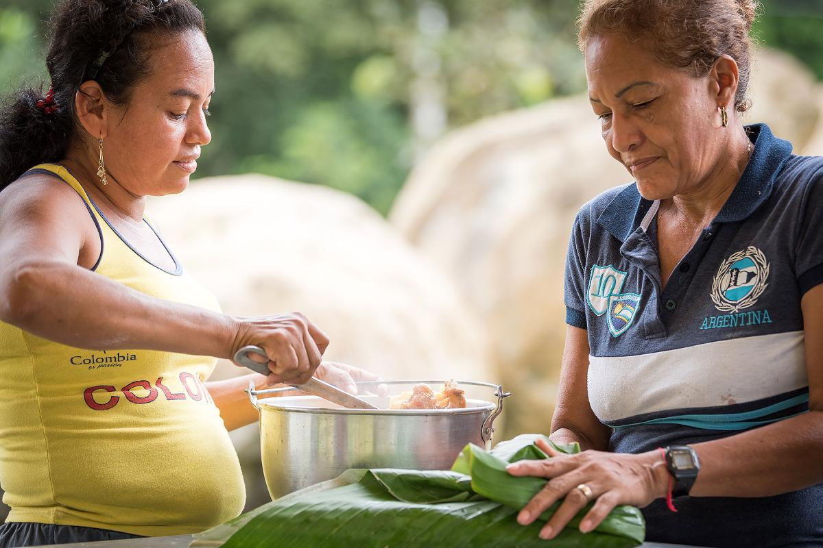 Mayerlis serves woman leader Aida a meal of sarapa – rice and chicken wrapped in a Cachibou leaf. Photo: LWF/Albin Hillert