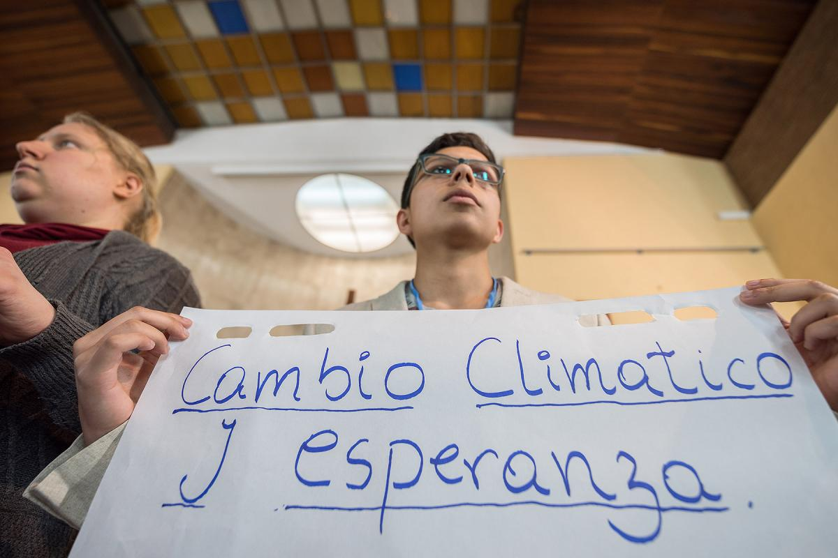 """""""Cambio Climático y Esperanza"""" ('Climate Change and Hope') reads the text, as Lutheran World Federation delegate Sebastian Ignacio Muñoz Oyarzo from the Evangelical Lutheran Church in Chile holds a sheet of paper on which key discussion points have been summarized at an interfaith dialogue in Madrid, 1 December. All photos: LWF/Albin Hillert"""
