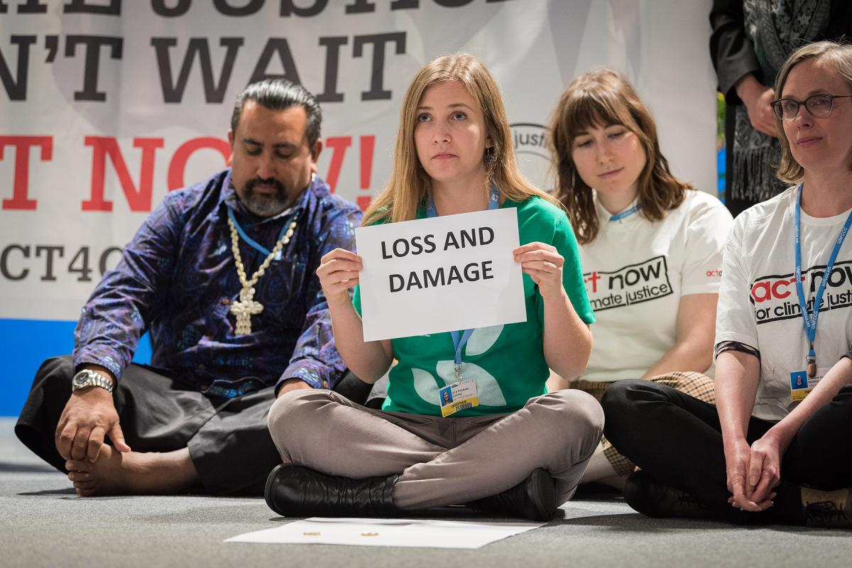 """Erika Rodning from the Evangelical Lutheran Church in Canada illustrates the lack of balance in finance of the global climate response during a stunt at COP25 in Madrid, Spain. Most of the finance is put into mitigation, some into adaptation, but very little into loss and damage, even though """"that's where the people are"""". Photo: LWF/Albin Hillert"""