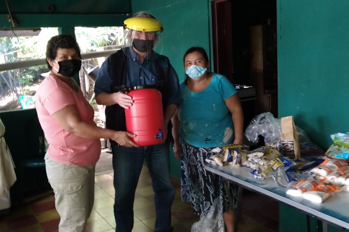 Hans-Jürgen Johnke (middle), Mission EineWelt staff working in El Salvador, hands over food and a canister for washing hands to members of the congregation in El Volcan. Photo: MEW