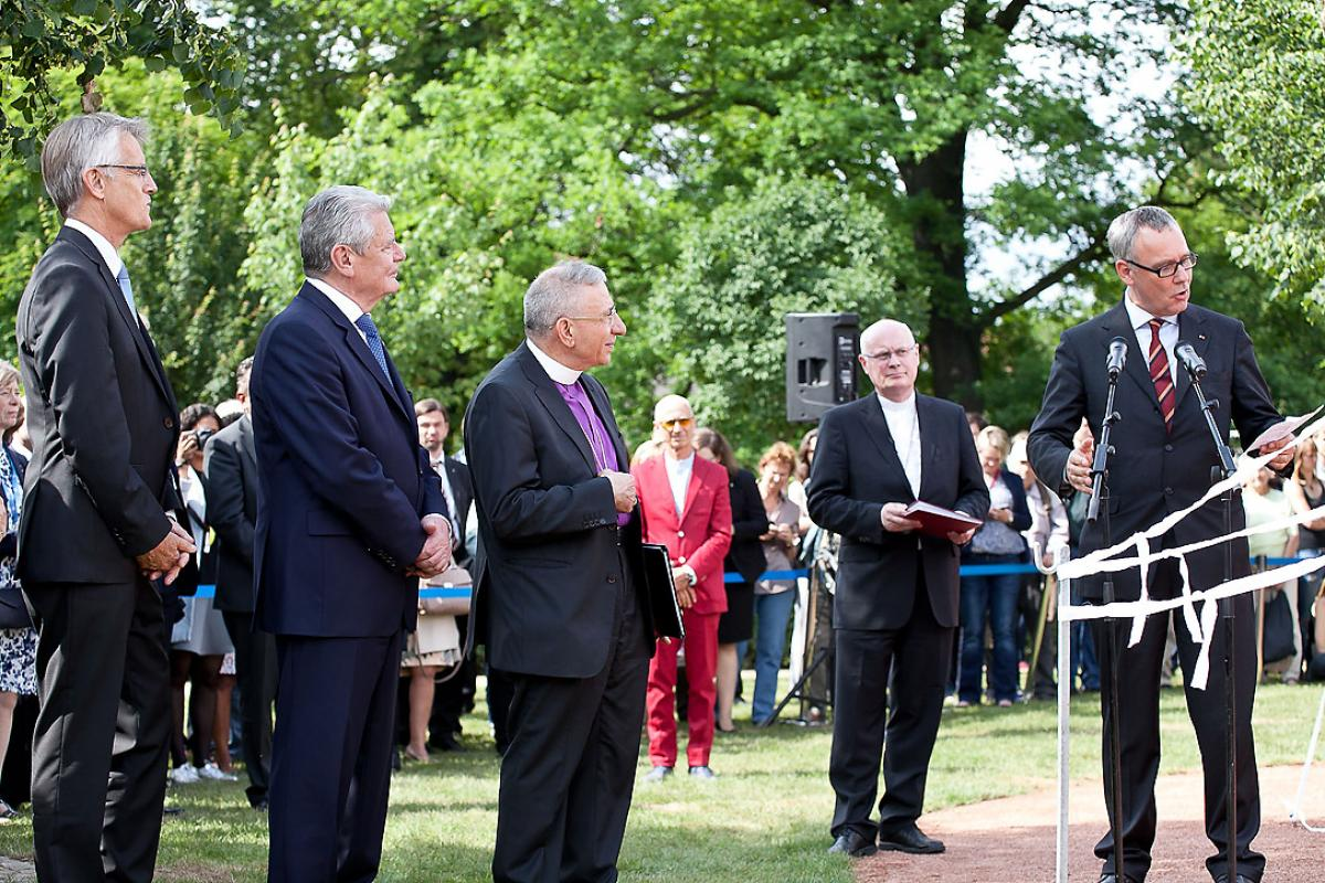 Luther Garden architect Andreas Kipar, right, explains the elements of the art installation, Heavenly Cross, moments before it is unveiled. Looking on are LWF General Secretary Martin Junge, left, German President Joachim Gauck, LWF President Bishop Dr Munib A. Younan and General Secretary of the German National Committee of the LWF, Norbert Denecke, during the unveiling of the Heavenly Cross in the Luther Garden in Wittenberg, Germany. Photo: LWF/Marko Schoeneberg