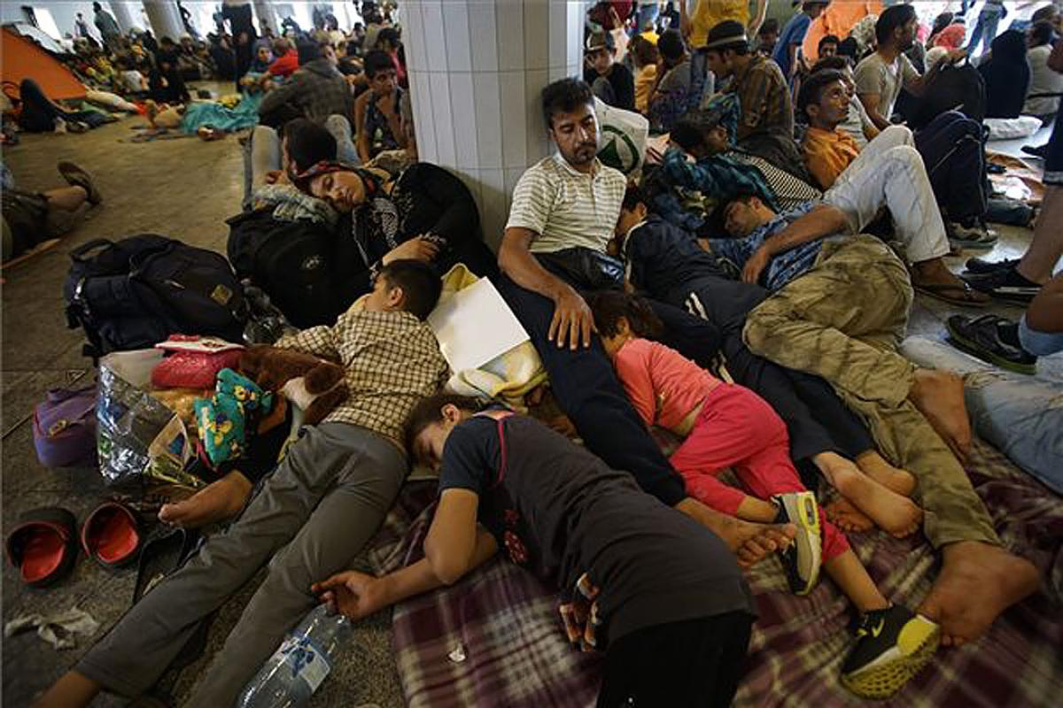 Refugees lie exhausted in a public place in Hungary, en route to northern European countries. Photo:MTI