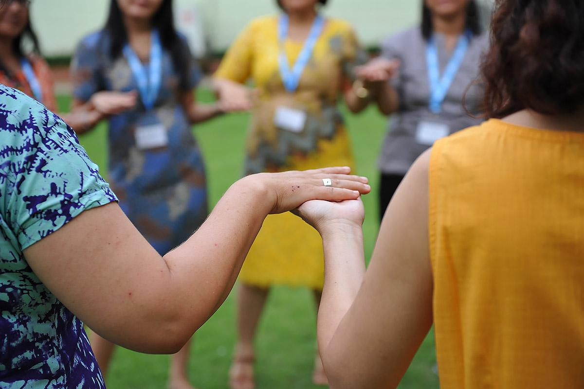 Women from LWF member churches in Asia take part in an exercise, holding hands. Photo: LWF/A. Danielsson
