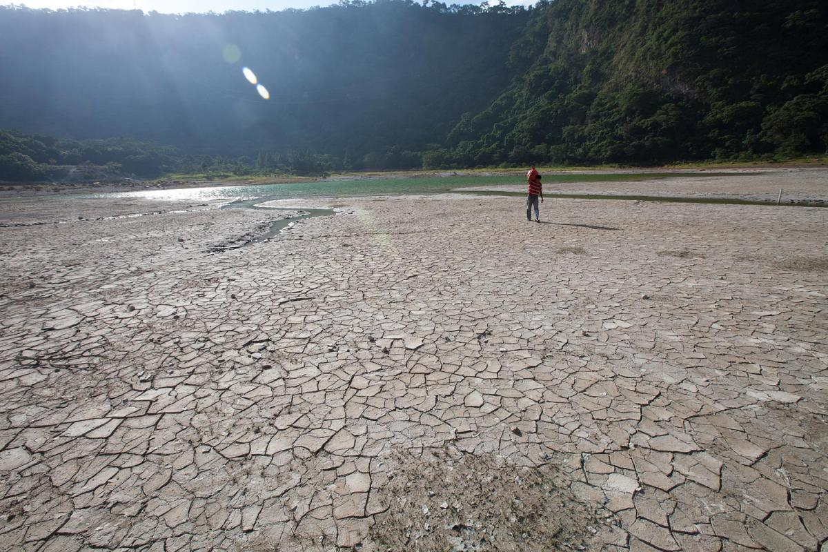 """At the lagoon of Alegría, Usulután, El Salvador, water levels have dropped dramatically in the drought that is affecting the region. Here, where the water has receded hundreds of meters, a man carries a """"cantaro"""" of water across the dry lagoon bed. The effect of climate changes in the Central American region are already extreme. Photo: LWF/Sean Hawkey"""