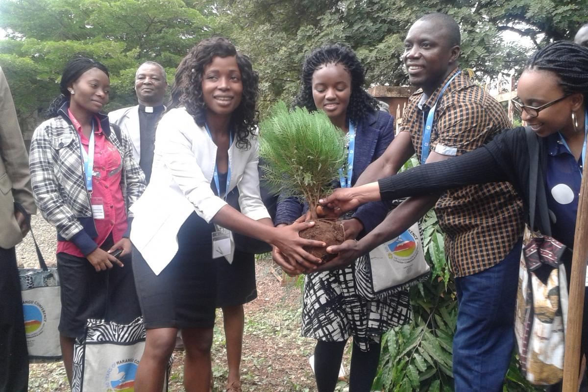 Global Young Reformers Network members plant a tree during an exposure visit to Majengo Parish in Moshi, Tanzania. From left: Sam Ofonime (Nigeria), Rev. Helvi Muremi (Namibia), Anderson Cooper (Liberia) and Sikhanyiso Mhaka (Zimbabwe). Photo LWF/Allison Westerhoff