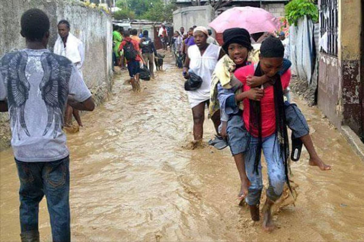 A survivor is carried to safety through a flooded street. Photos: LWF Haiti