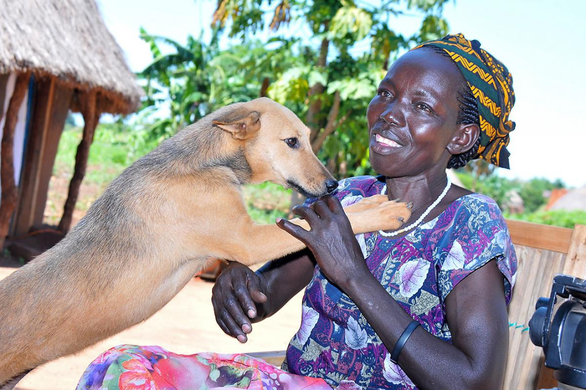 Molly Aringo with her dog. LWF has helped her embrace life again following a diagnosis of HIV. Photo: LWF/P. Kikomeko