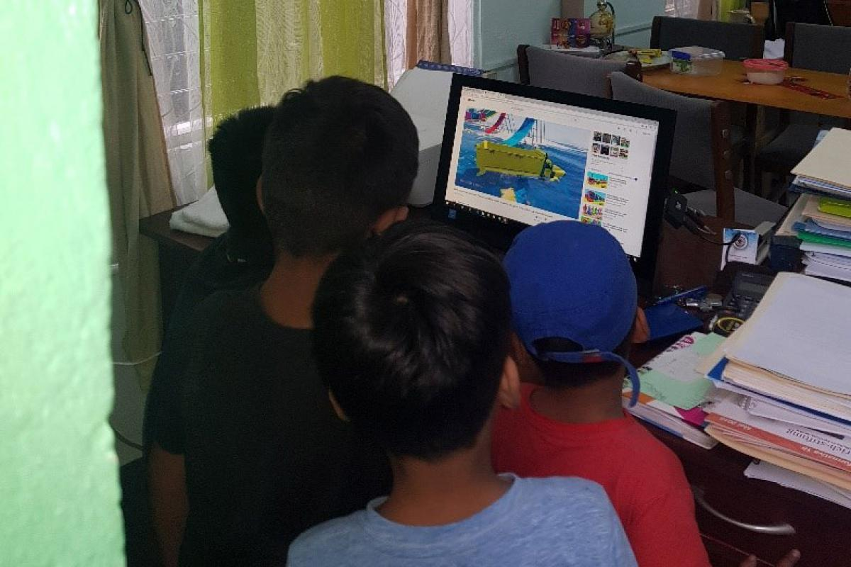 Children looking at a computer. Photo: ILCO