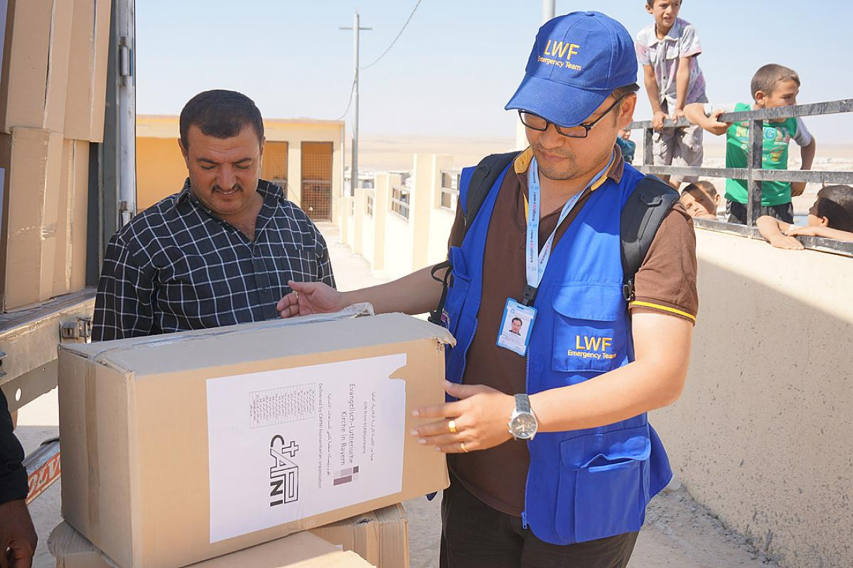 LWF assisting in the distribution of winter clothes sponsored by the Evangelical Lutheran Church of Bavaria in Khanki camp, Northern Iraq. Photo: LWF Iraq