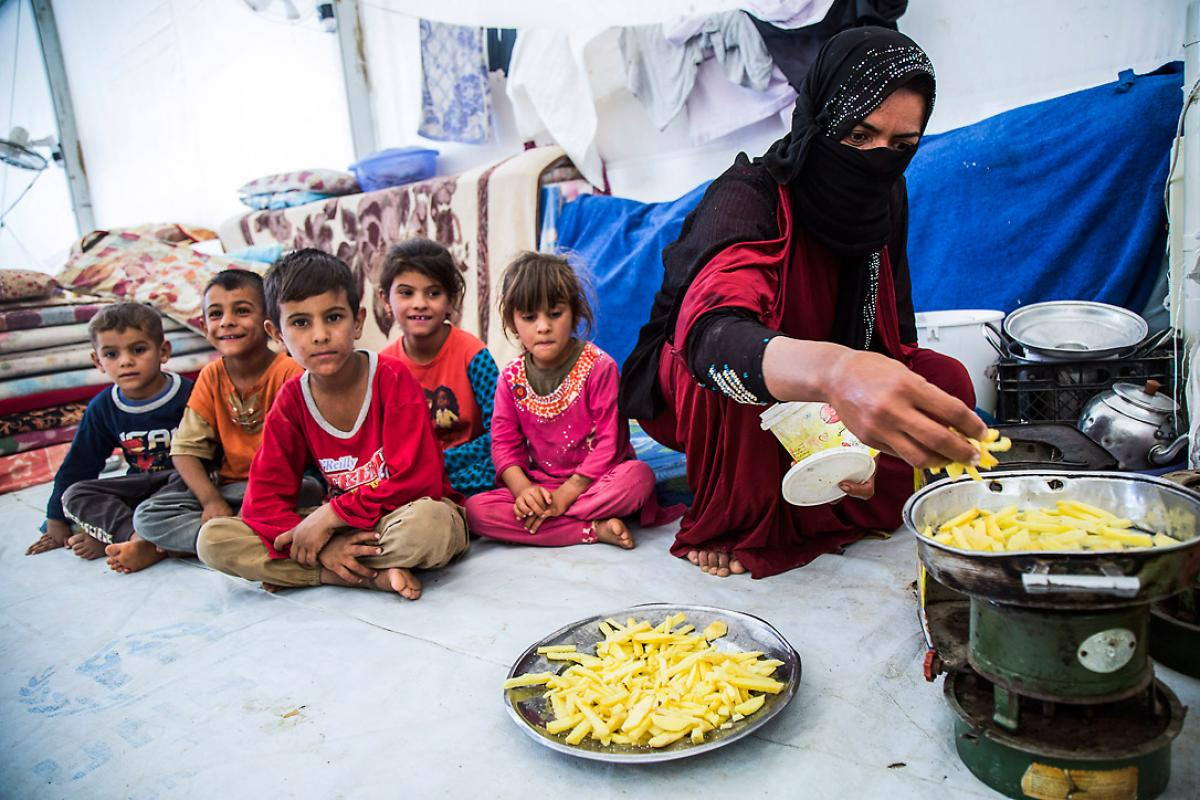 A mother prepares a meal for her children. The family fled from Mosul a few weeks ago and now lives in Debaga camp. All images: LWF/ Seivan Salim