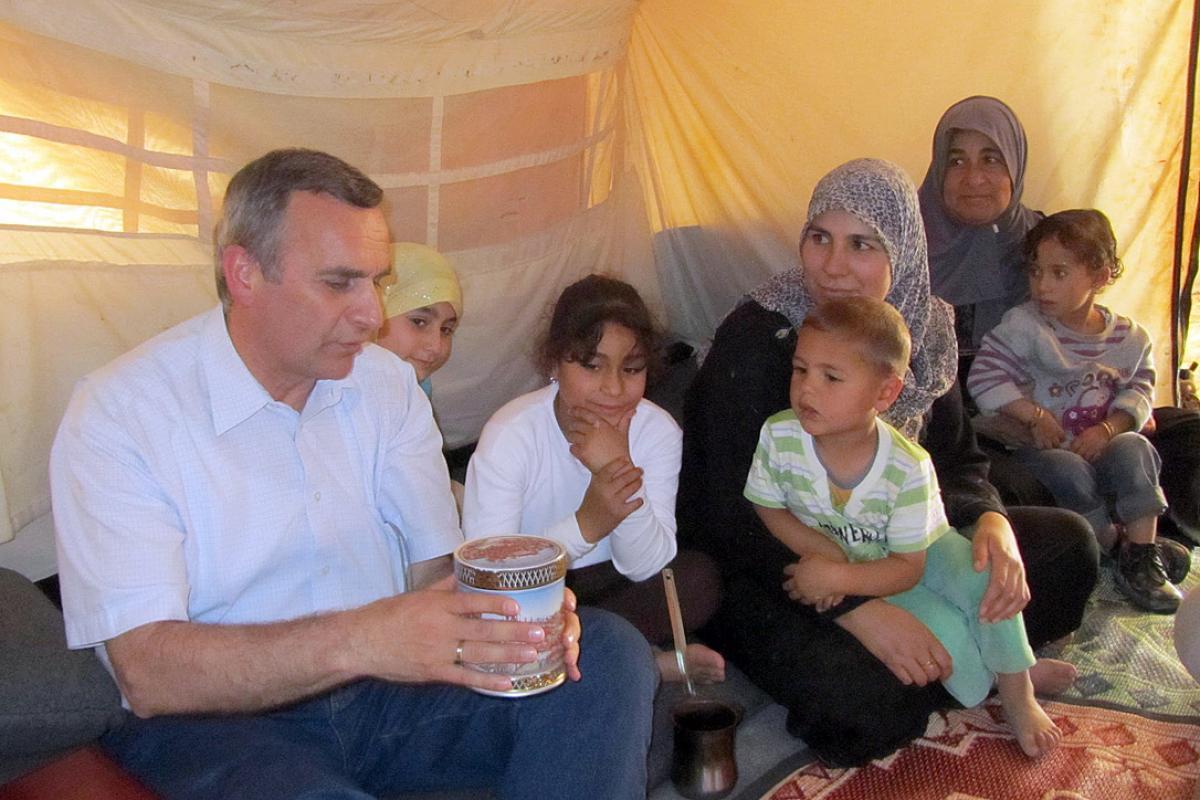 Rev. Michael Martin shares a tin of sweets with a Syrian family at the Za'atri refugee camp. Photo: LWF Jordan/E. Gano