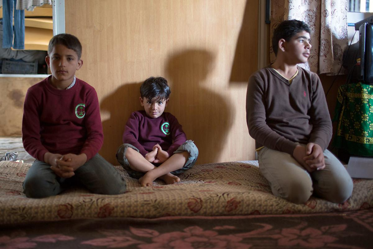 One half of all refugees at the Za'atari Camp are children. Three brothers from a Syrian family sit, hoping for an end to the conflict.  Photo: LWF/Maria de la Guardia