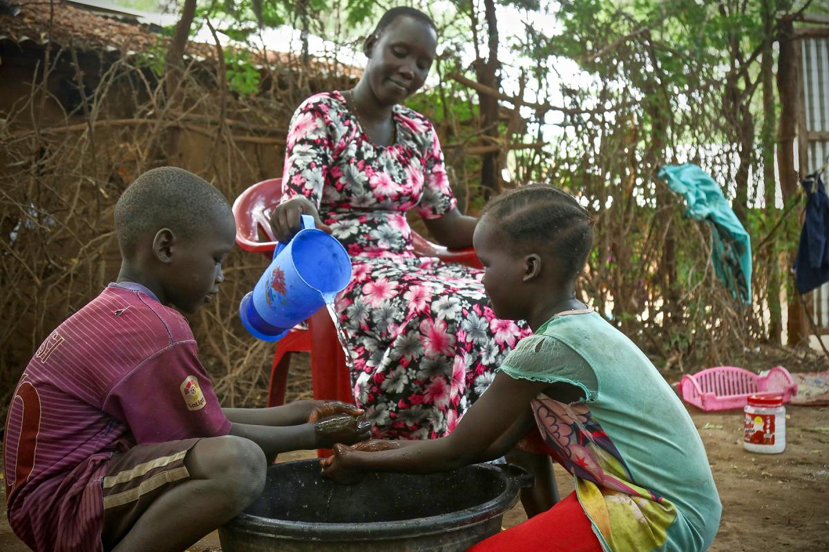 A woman washes her children's hands in Kakuma refugee camp, Kenya. LWF has reinforced hygiene education to prevent a spread of COVID-19 in the camp. Photo: LWF/ P. Omagwa
