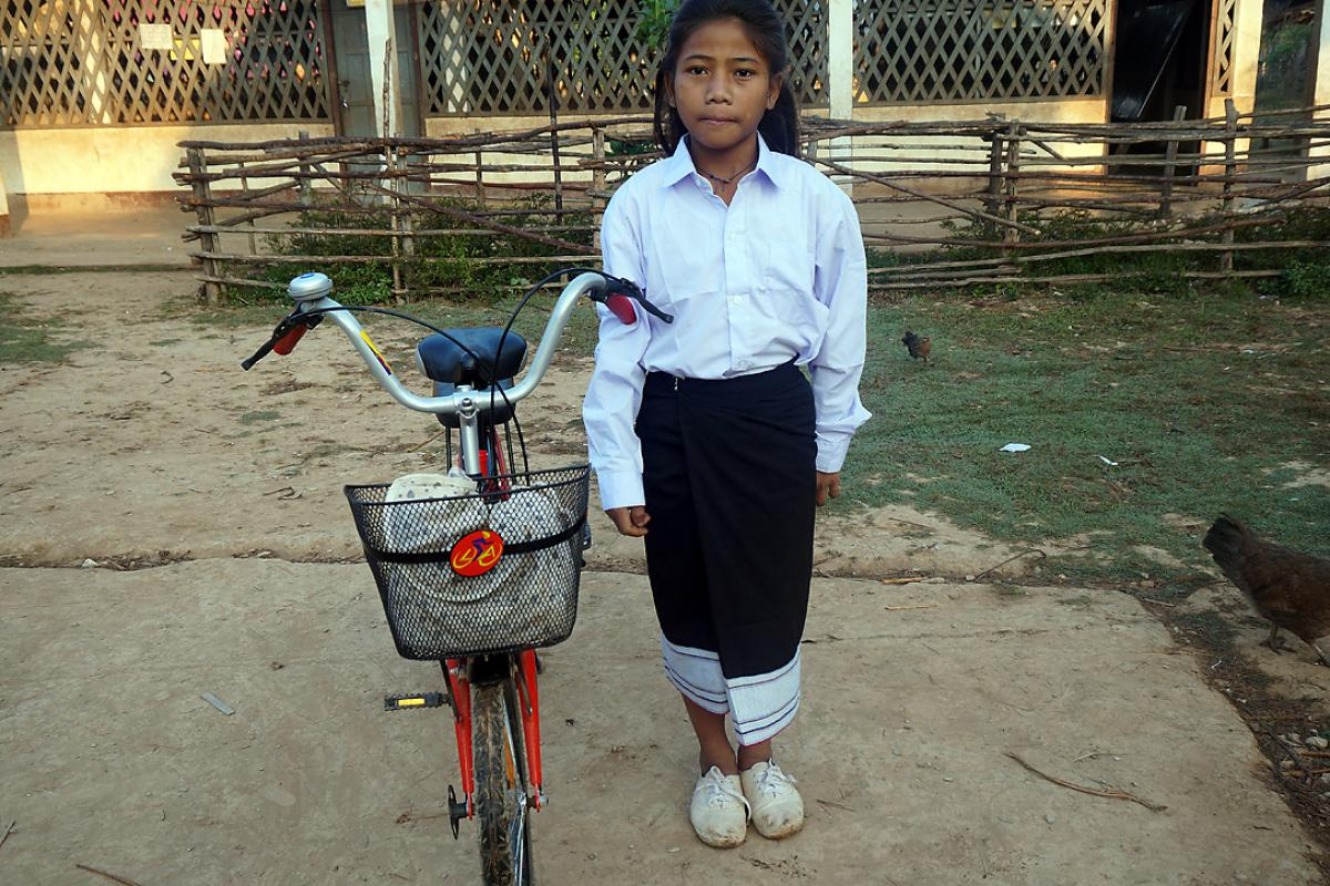 Chanset with her uniform and bicycle in front of her school. Photo: LWF/P. Simayvanh