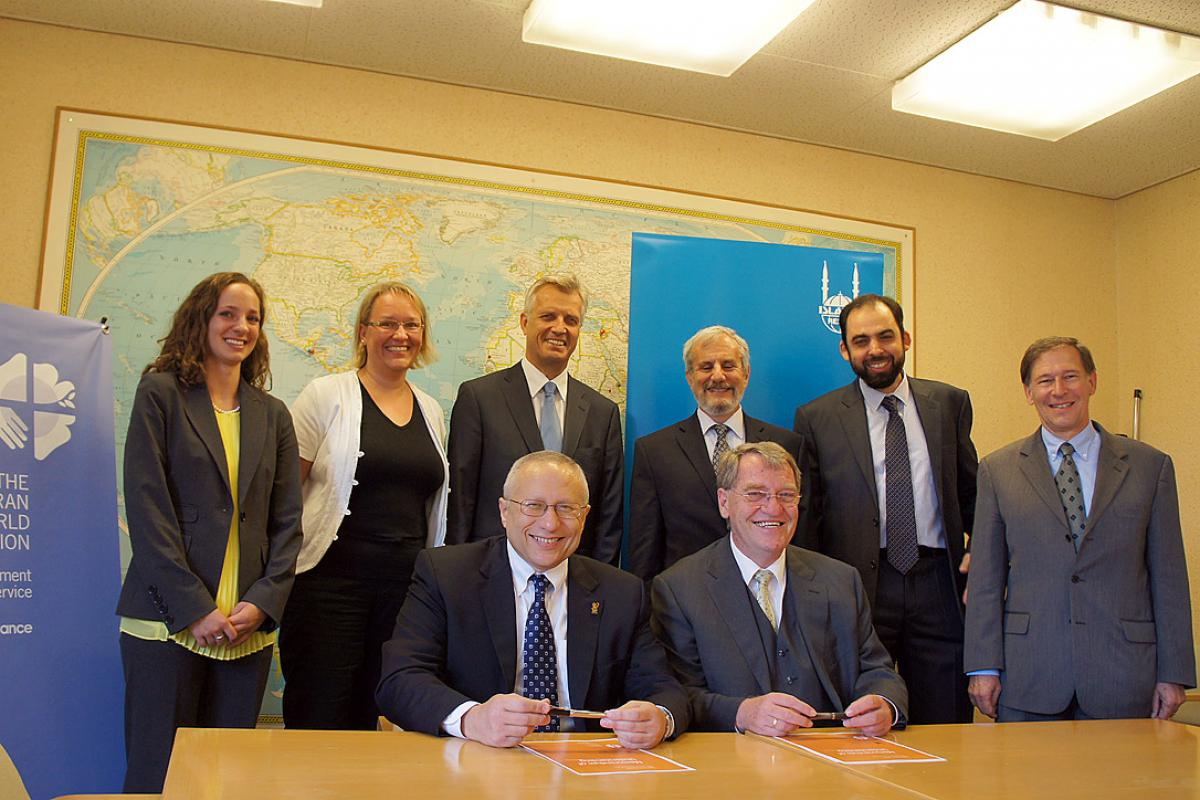 Signing of the MOU by Dr Mohamed Ashmawey, CEO of IRW and DWS Director Eberhard Hitzler (front, from left), witnessed by LWF Assistant General Secretary for Human Rights Affairs Ralston Deffenbaugh, Mehdi ben M'rad, IRW Director of National Programs, UNHCR Deputy High Commissioner Alexander Aleinikoff, LWF General Secretary Rev. Martin Junge, LWF Global program Coordinator Maria Immonen and LWF Program Assistant for Interfaith Cooperation Elizabeth Gano (from right). Photo: LWF/S. Gallay