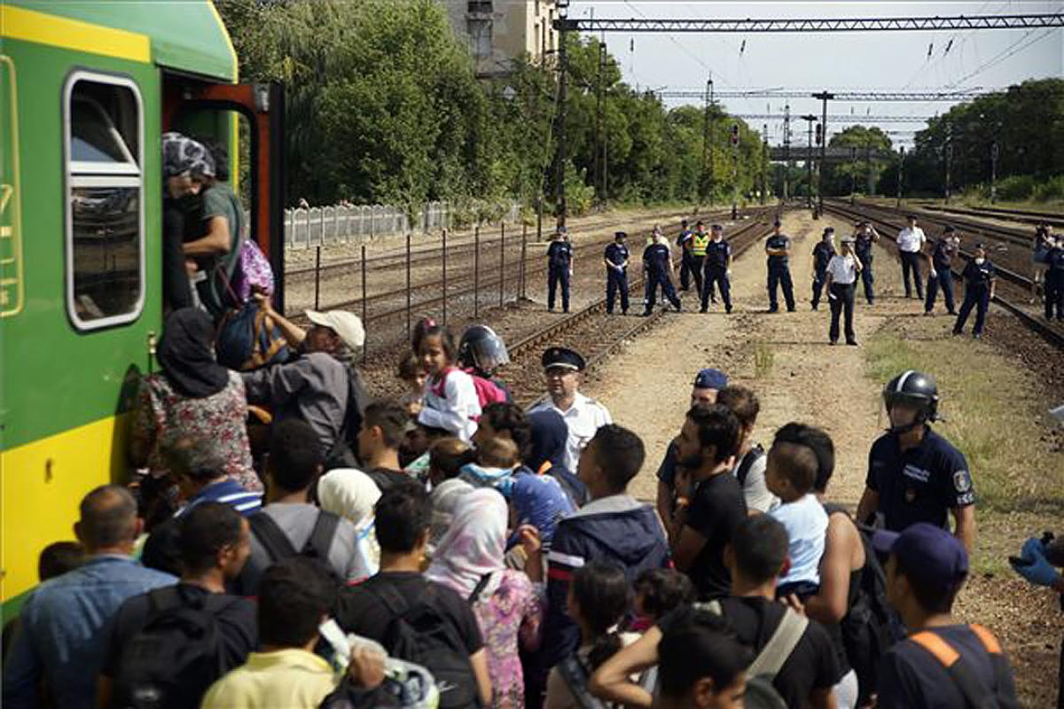 Hungarian police form a cordon as refugees board a train for northern Europe. Photo: MTI