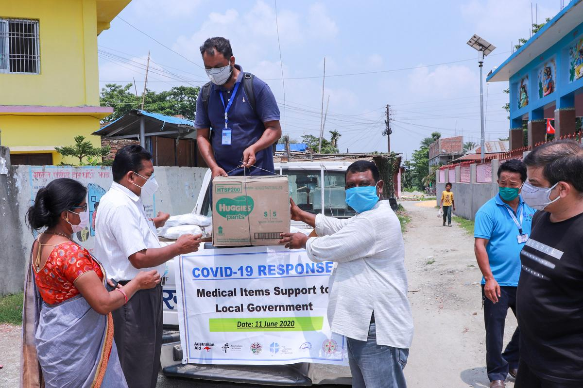 NELC President Rev. Joseph Soren (right) presents packages of medical items and hygiene kits to leaders of Jahada Rural Municipality in Morang district, eastern Nepal. Photo: LCWS/Suman Rai
