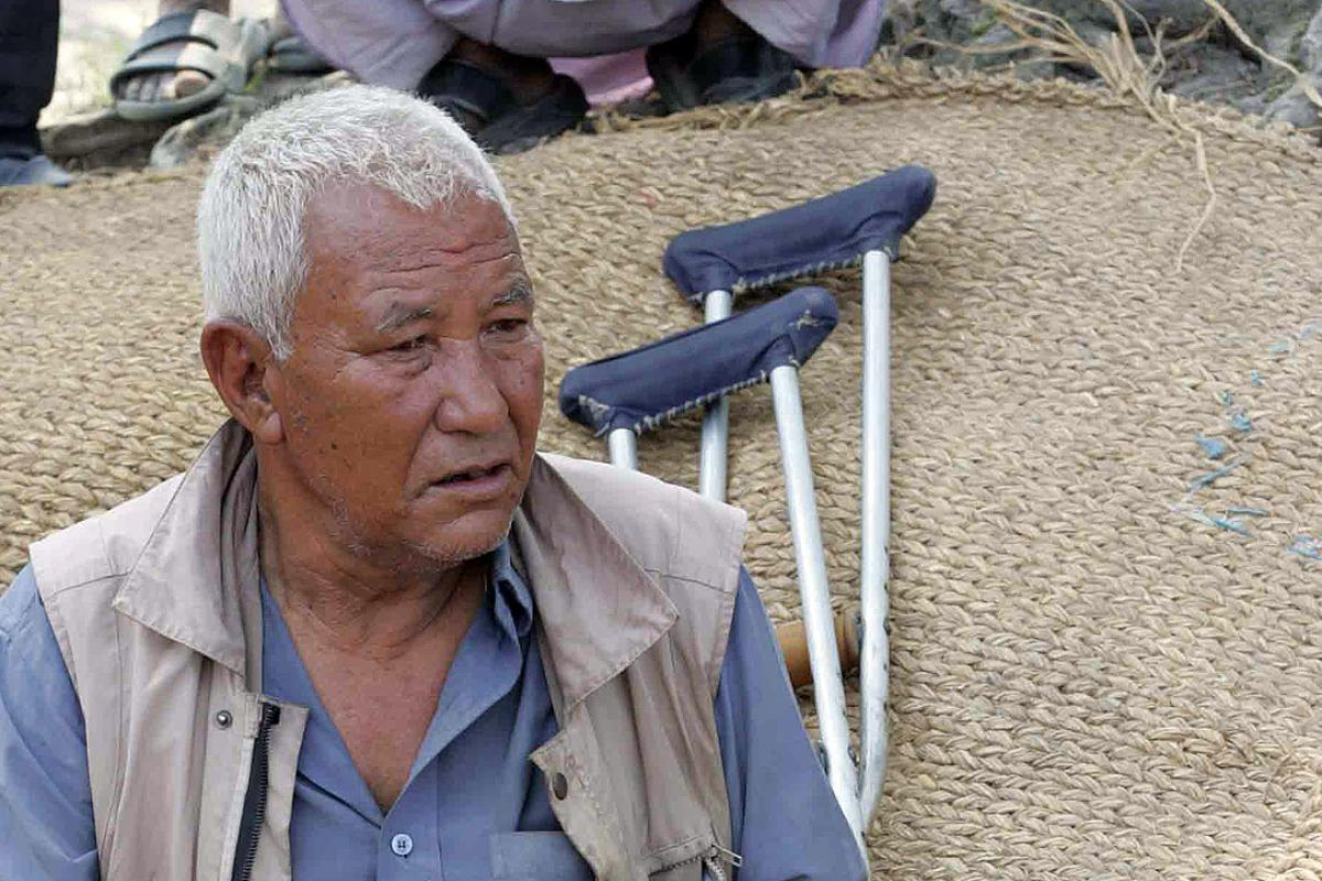KC sitting in front of his destroyed house. Photo: Kosh Raj Koirala