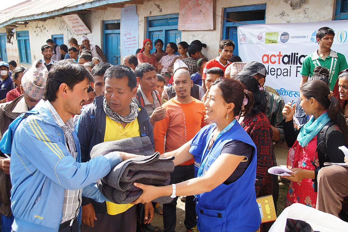 LWF staff offer blankets to earthquake survivors in Lalitpur district. Photo: LWF/C. Kästner