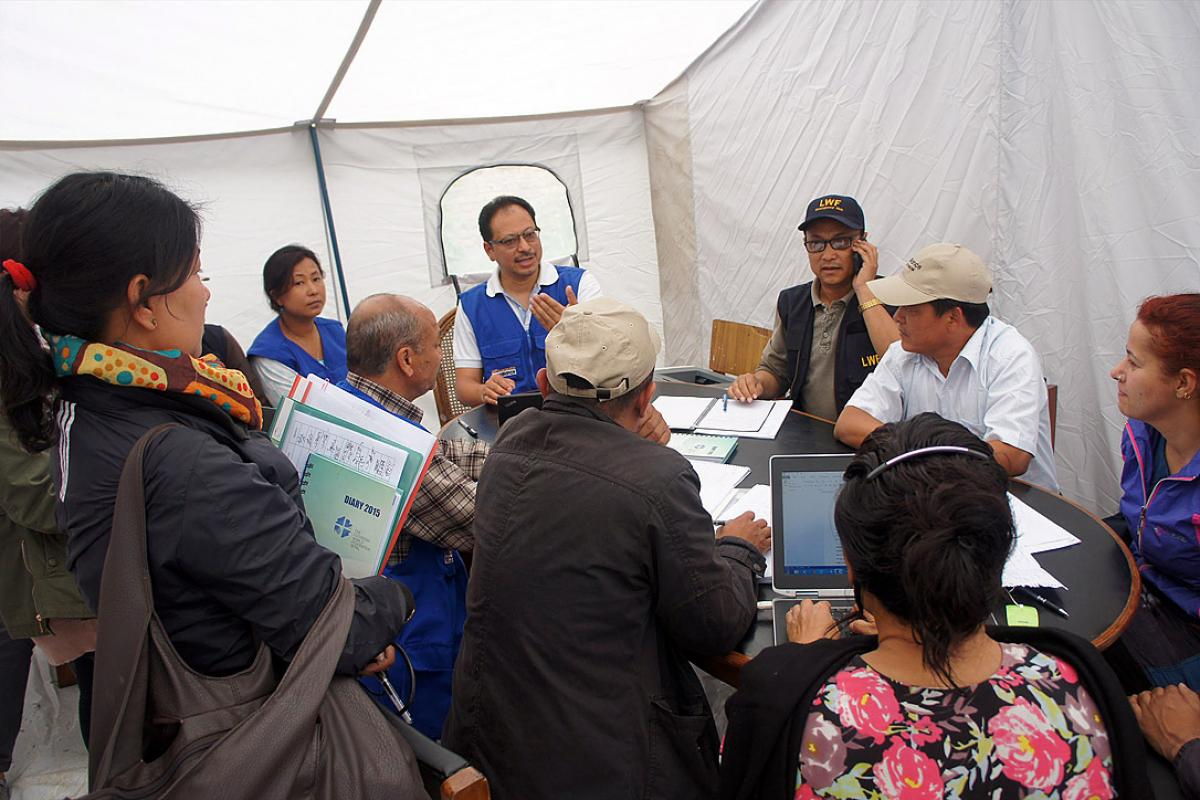 LWF Country Director Nepal, Dr Prabin Manandhar, (center, with blue vest) at a team meeting coordinating the LWF earthquake relief work. Photo: LWF/C. Kästner