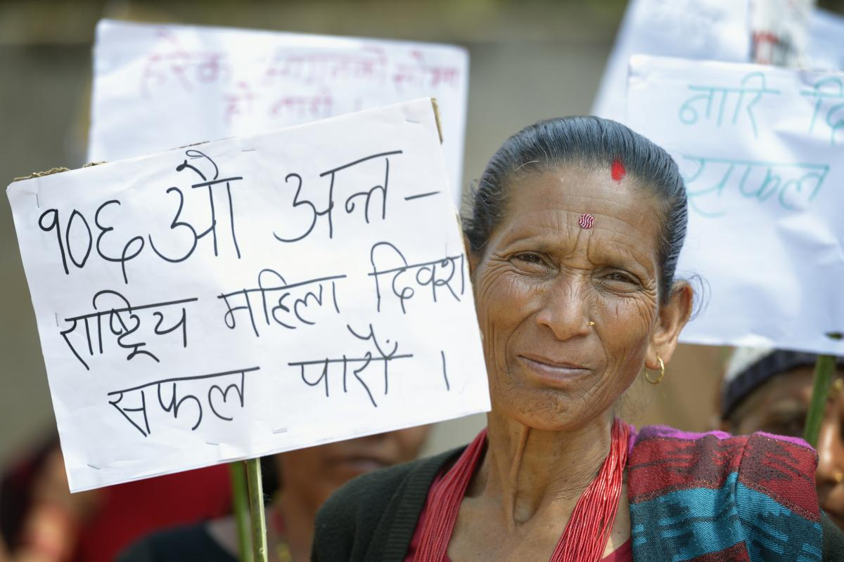"""""""Let's make the Women's Day a success."""" A woman holds a sign during a march celebrating International Women's Day in Dhawa, a village in the Gorkha District of Nepal. ACT / P. Jeffrey"""