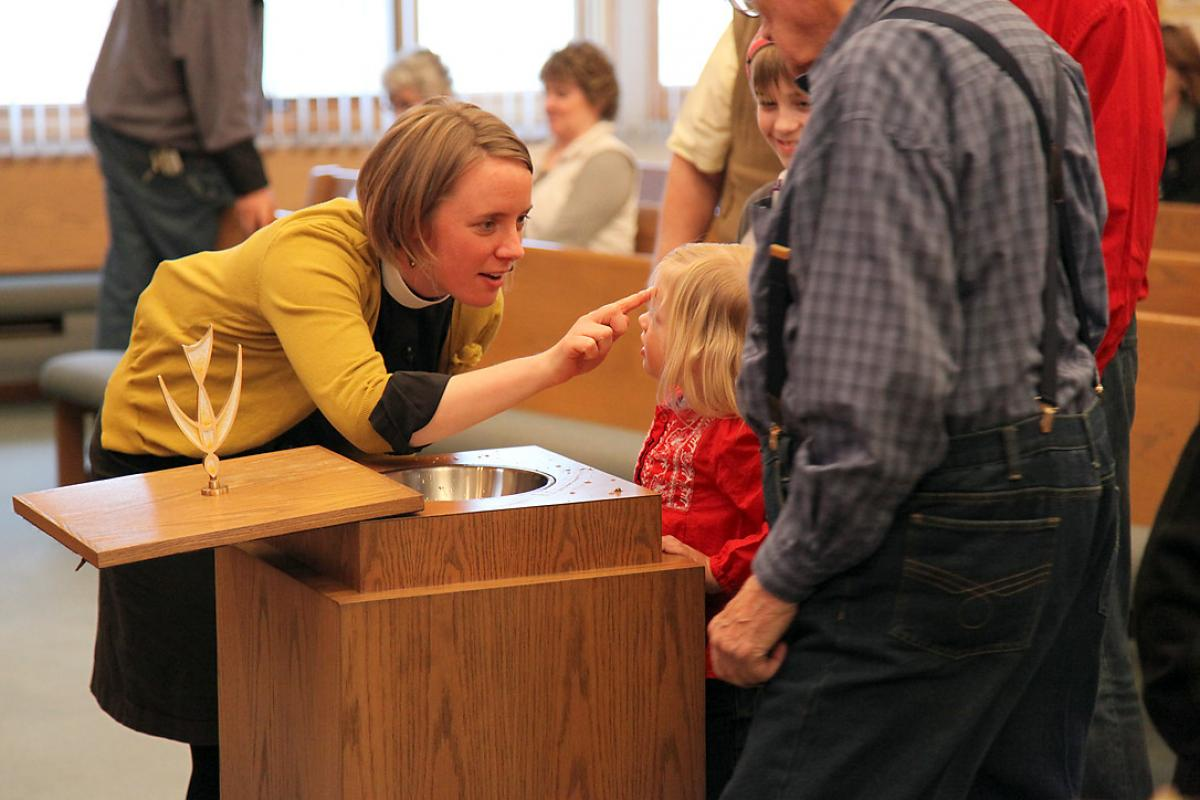 Rev. Taryn Montgomery making the sign of the cross on her daughter's forehead at the Bread of Life Lutheran Church in Minot, North Dakota, United States. Photo: ELCA