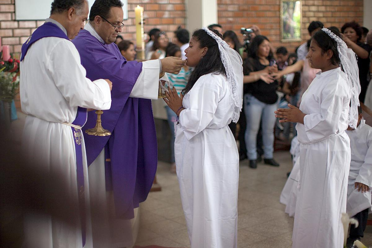 Lutheran pastor Rev.  Pedro Bullón (left) and  Catholic priest Fr. Marco Agüero Vidal (right) preside at the joint First Communion in Pamplona Alta, Lima, December 2014. Photo: LWF/Sean Hawkey