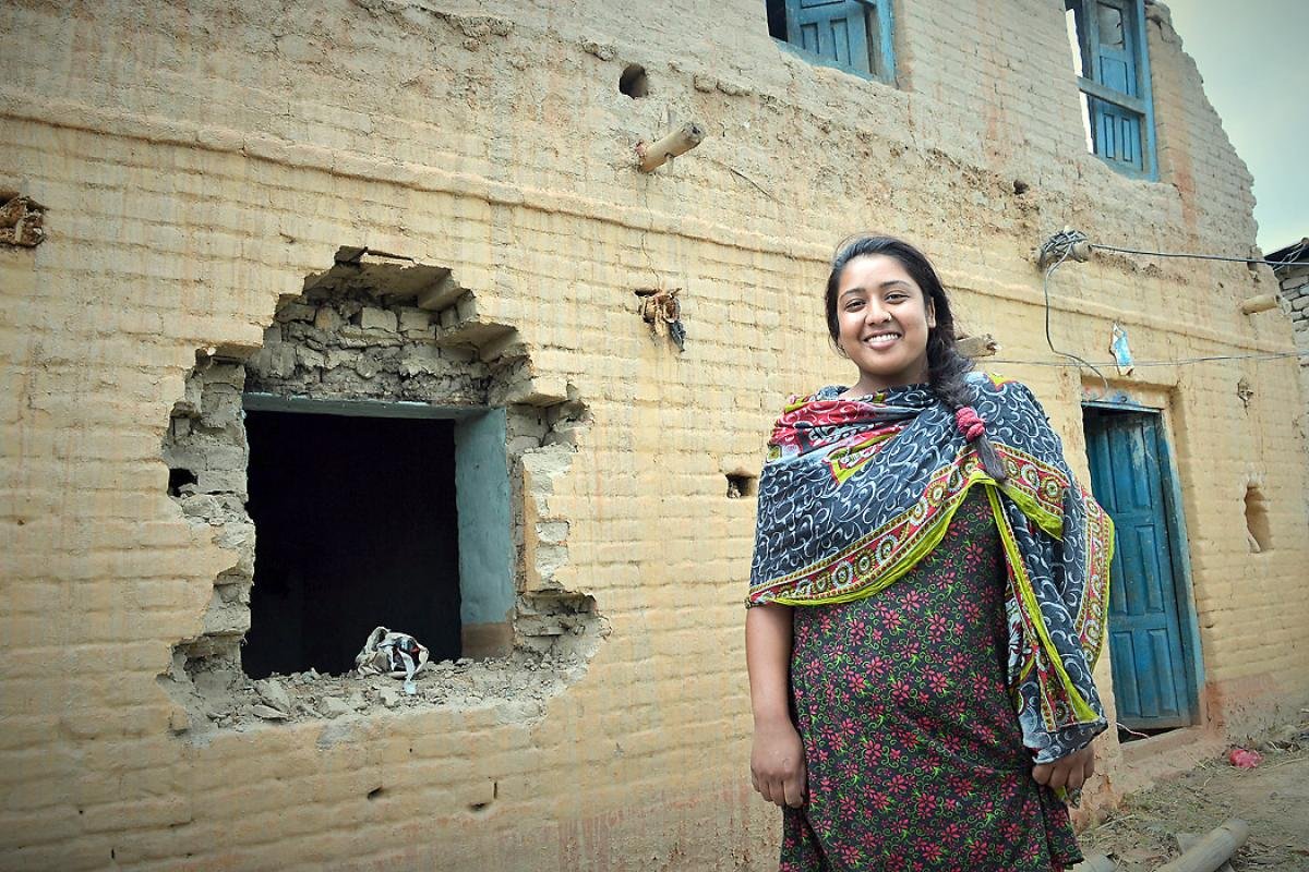 Rosni Paryar, in front of her partially destroyed home. She fear she will remain unemployed because she of the Dalit caste. Photo: LWF/Lucia de Vries