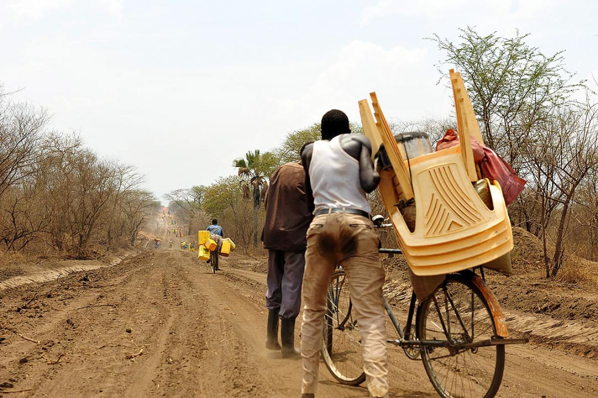 A refugee carts goods toward Uganda