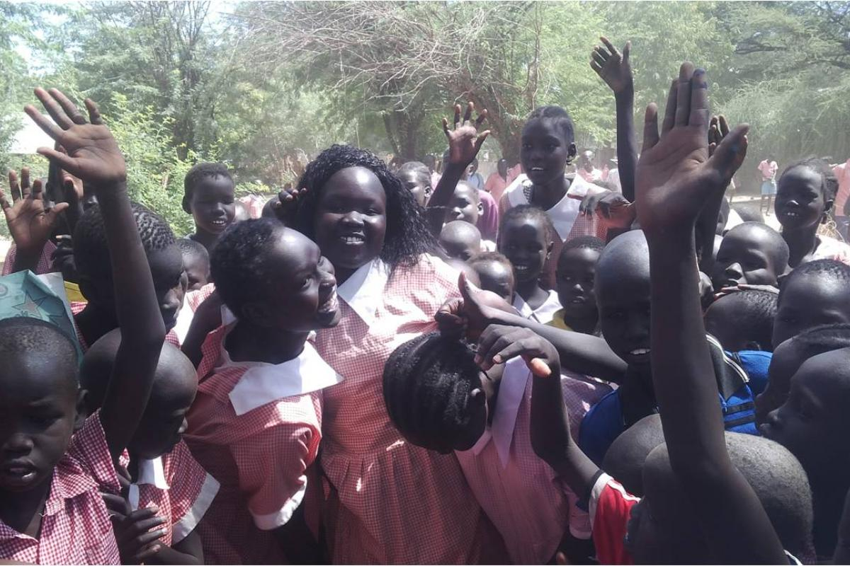 Margaret Awak Aguer is mobbed and lifted by fellow students at Shambe Primary School after emerging as the best candidate in Kakuma Refugee camp in the 2015 KCPE with 400 out of a possible 500 marks © LWF Kakuma January 2016