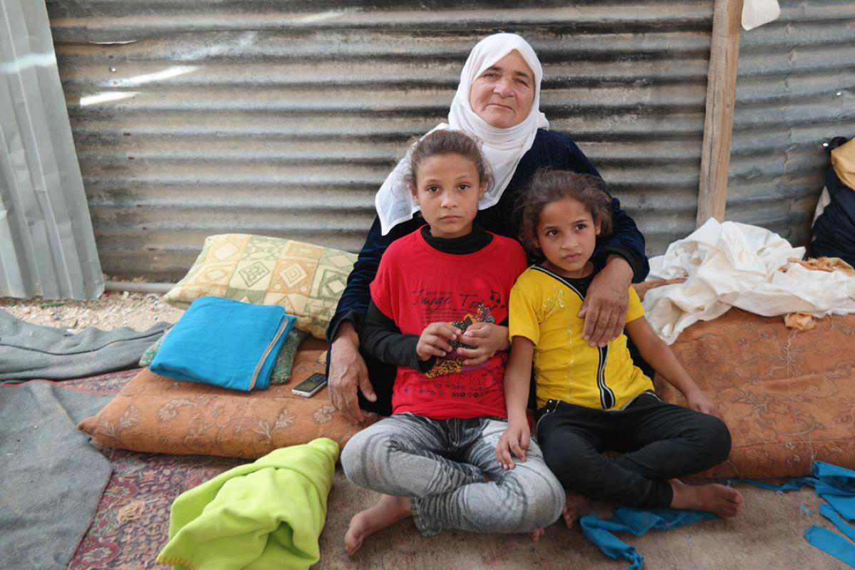 Salam (left, in red T-Shirt) with her grandmother and younger sister in their shelter in Za'atari camp. Photo: LWF Jordan/D. Odén