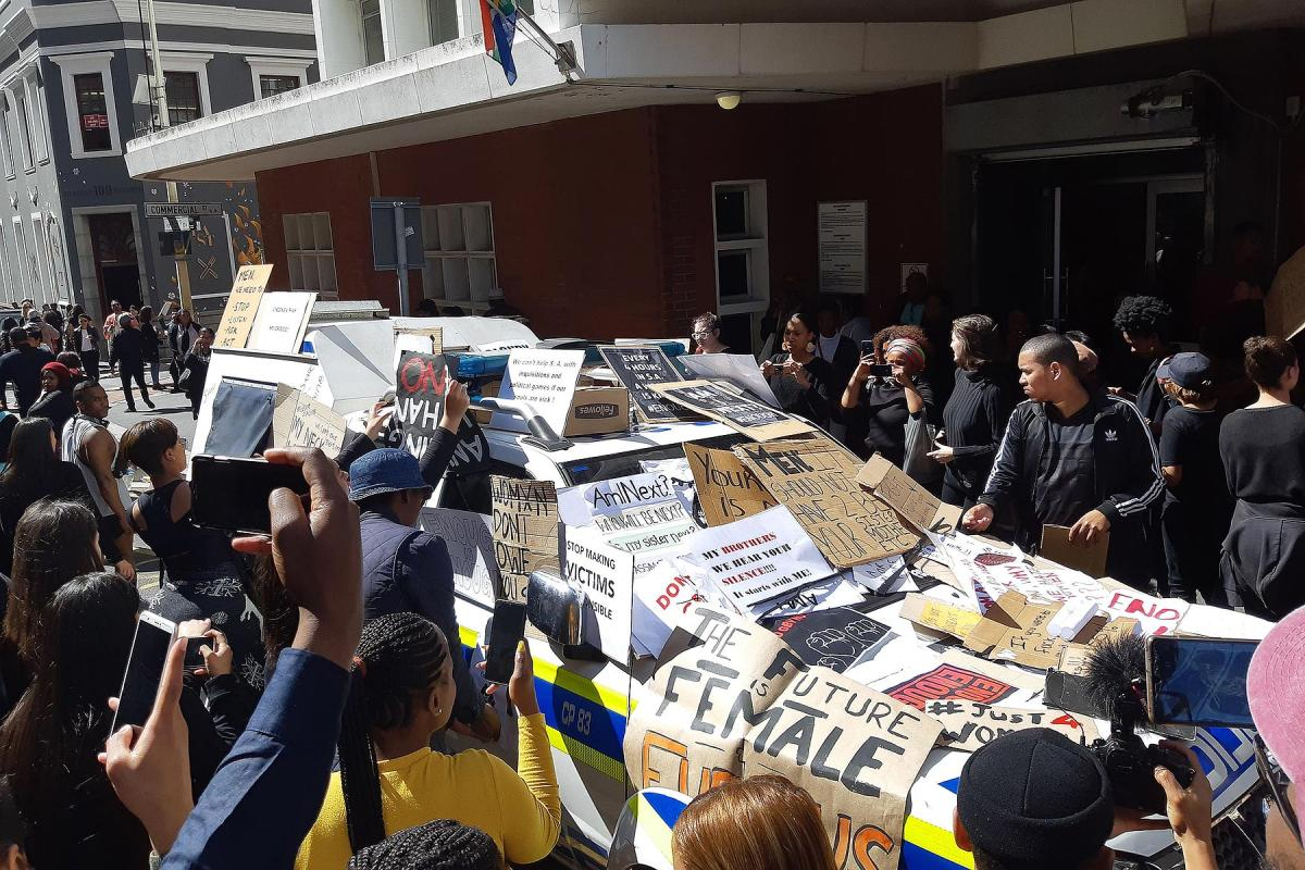 The anti-femicide demonstration in Cape Town, South Africa following the death of Uyinene Mrwetyana. Protestors cover a police vehicle with placards. Photo: Discott, via Wikimedia Commons (CC-BY-SA)