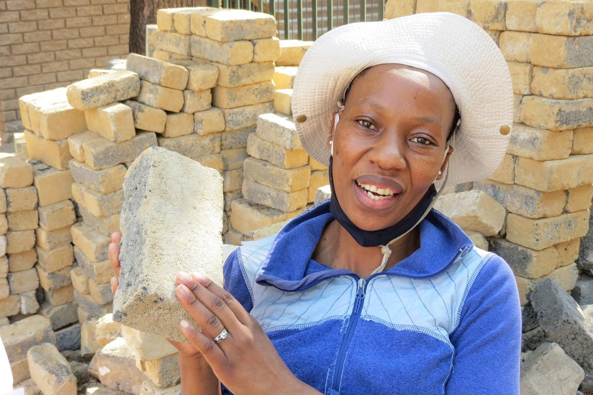 Bricklayer Makhatutu Siimane, showing what she can do with bricks. Photo: Outreach Foundation