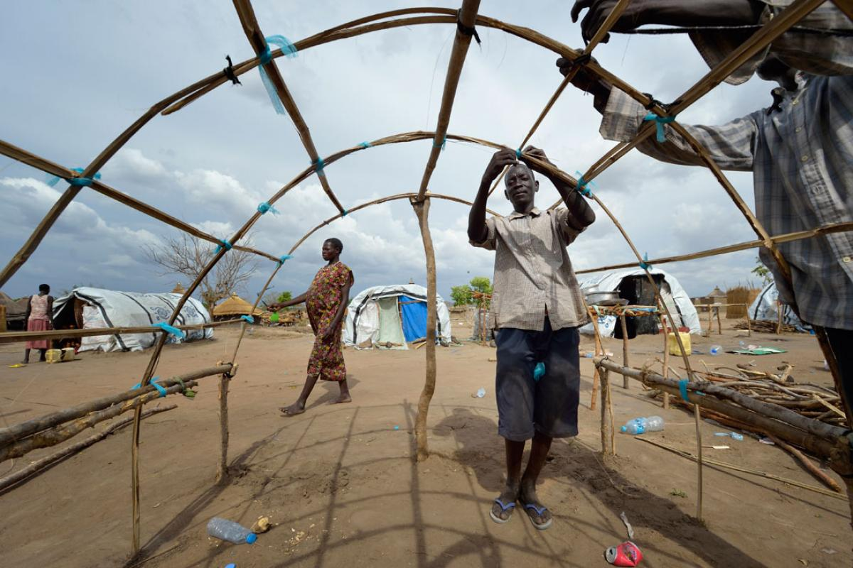 Men in South Sudan reconstruct their house after the village was destroyed in Jonglei. Photo: ACT/ Paul Jeffrey