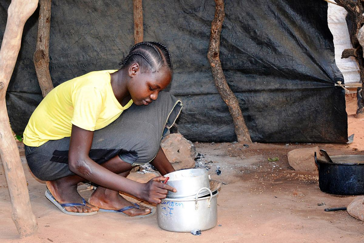 Sudanese refugee Amona Tia prepares the evening meal for her siblings at the Ajuong Thok refugee camp in South Sudan. With help from the LWF, she has resumed schooling. Photo: LWF/A. Kiura